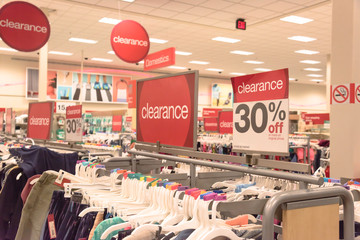 Red clearance sign for 30% off on cloth rack with variety of women apparel in retail store in America.
