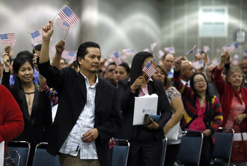 Immigrants wave U.S. flags after taking the oath of citizenship during a naturalization ceremony to become new citizens of the U.S. in Los Angeles