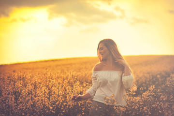 Smiling woman in yellow rapeseed field at sunset