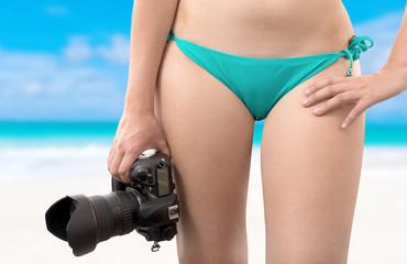 beautiful woman in swimsuit holding digital photo camera