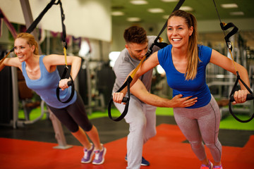 Personal trainer assisting young woman while exercising with suspension in the gym