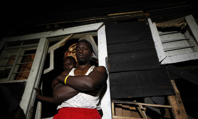 A man stands outside the ruins of his house struck by a mortar bomb during an operation in Goma