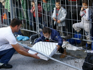 A waiter serves a pizza to a group of migrants at the Austrian border near the Slovenian village of Sentilj
