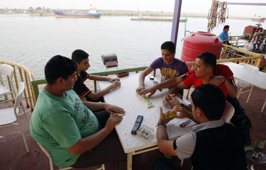 Young men play dominoes at a floating cafe on a ferry docked on the shores of the Shatt al-Arab waterway in Basra