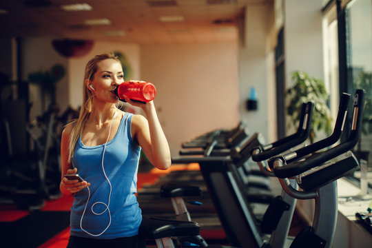Beautiful young woman resting and drinking water in the gym