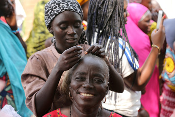 A woman plaits another woman's hair at a camp for internally displaced people in Abuja