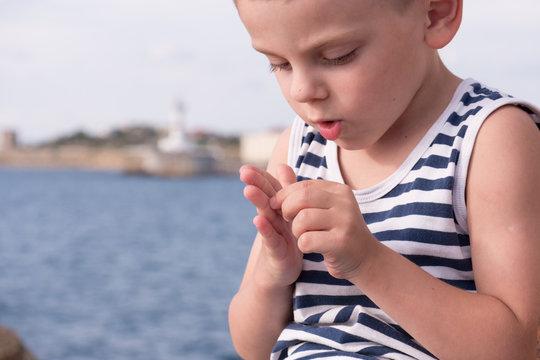 Attentive little boy gets a splinter from his finger