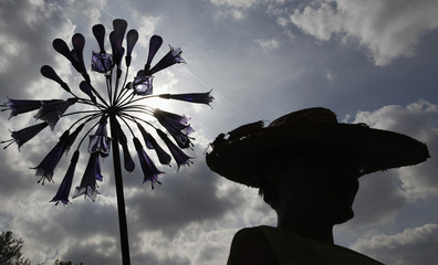 A gardener is silhouetted next to a glass flower as preparations were underway for the Chelsea Flower Show in London