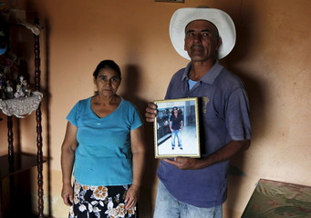 Benjamin Aceituno and his wife Ana Rodas pose with a picture of their missing son on the dangerous journey to the United States through Mexico, at the town of the Ermita outside Tegucigalpa