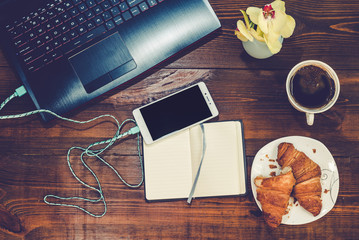 Workspace with laptop, smartphone, croissant, cofee on a wooden desk