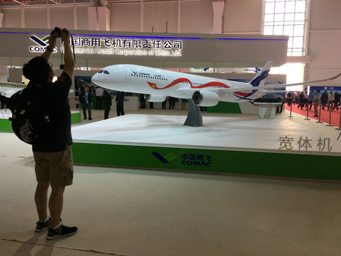 A man takes picture of the model of a widebody jet, which is planned to be developed by COMAC and Russia's UAC at an air show, the China International Aviation and Aerospace Exhibition, in Zhuhai