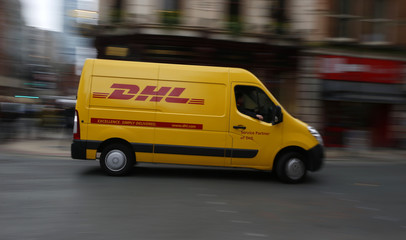A DHL delivery van drives along a road in Manchester northern England.
