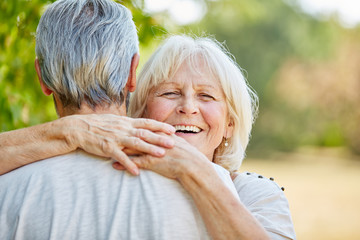 Smiling senior woman hugging a man