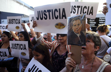 A woman holds up a picture of late Argentine prosecutor Alberto Nisman outside the AMIA Jewish community center during a demonstration to demand justice over Nisman's death in Buenos Aires