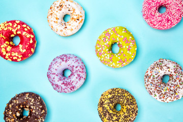 Donuts glazed with sprinkles on pastel blue background.