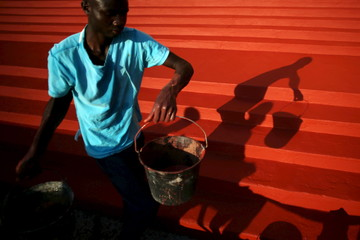 Man paints the stairs in front of the Notre Dame Immaculate Conception Cathedral, where Pope Francis will visit, in Bangui
