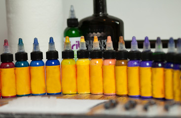 Multiple bottles with colorful inks for tattoo, close up view. Selective focus.