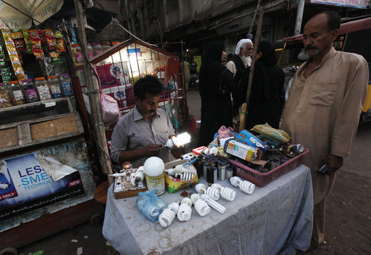 Usman Ghani checks an energy saving bulb, after repairing it for a customer, at his makeshift stall in Karachi's slum