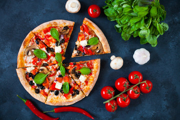 Homemade pizza with tomatoes, mozzarella and basil. Top view with copy space on dark concrete background.