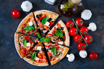Hot testy pizza with tomatoes, mozzarella, mushrooms, olives, red pepper and basil on black concrete background. Copyspace. Top view.