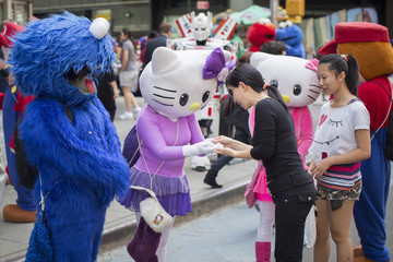 Characters dressed up as Cookie Monster from Sesame Street and Hello Kitty ask for tips after posing for pictures in Times Square in New York