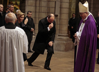Prince Albert II of Monaco and his wife Princess Charlene make the sign of the cross as they arrive with Archbishop Bernard Barsi at Monaco cathedral for an ecumenical mass in memory of late South African President Nelson Mandela in Monaco