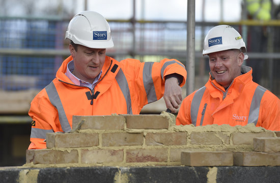 Britain's Prime Minister David Cameron lays bricks during a campaign visit to a home building scheme in Lancaster, northern England