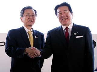 ANA President Shinobe shakes hands with JAL President Ueki at Haneda airport in Tokyo