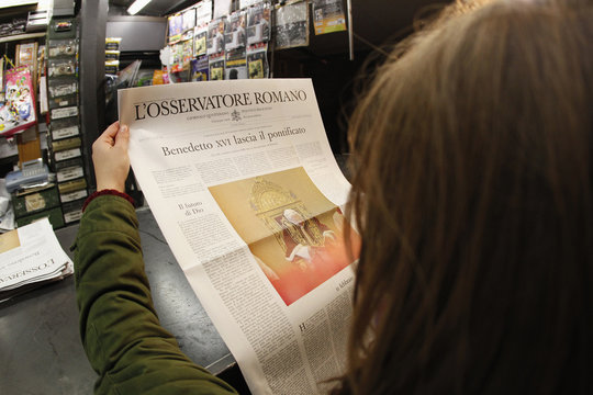 A woman reads the front page of Osservatore Romano newspaper in Rome