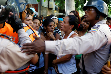 People gather to try to buy food outside a store in Caracas