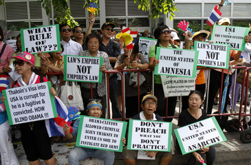 Members of Anti-Thaksin group shout slogans and hold placards during a rally outside the U.S. embassy in Bangkok