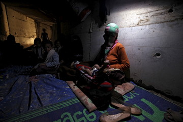 A woman holds her daughter inside an underground water tunnel with other displaced Yemeni families, after they were forced to flee their home due to ongoing air-strikes carried out by the Saudi-led coalition in Sanaa