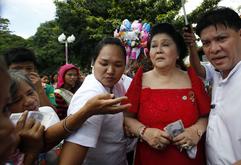 Former first lady Imelda Marcos holds money for her supporters in Batac
