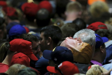 An audience member wears a mask of U.S. Republican presidential candidate Donald Trump at a campaign rally in Hartford