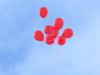 Red balloons flying in the sky.