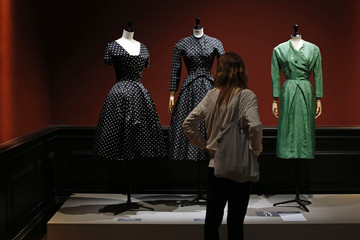 """A visitor looks at vintage dresses by designers Christian Dior, Jacques Heim and Givenchy presented in the exhibition """"Les Annees 50, La mode en France"""" at the Palais Galliera  fashion museum in Paris"""