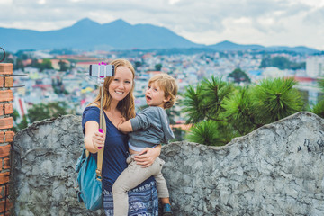 Young woman and her son taking smart phone self portrait pictures with selfie stickon the background of the city of Dalat, Vietnam
