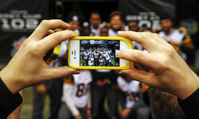 A woman uses a mobile phone to photograph Hamilton Tiger-Cats players during their team's practice at the CFL's 102nd Grey Cup week in Vancouver