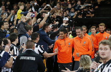 Fans of Italian Serie A soccer champions Juventus watch as the team enters the pitch before a training session in Sydney