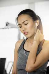 Asian woman in sportswear having neck pain at the gym.