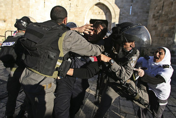 Israeli border policemen scuffle with Palestinian medics during clashes at a protest outside Jerusalem's Old City