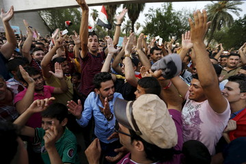 Iraqis shout slogans during a demonstration against power cuts amid an intense heatwave at Tahrir Square in central Baghdad