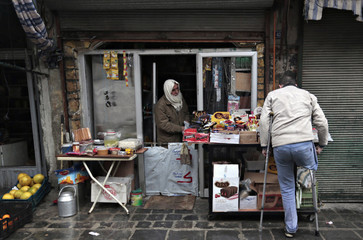 A handicapped man buys goods from a grocery shop in Old Aleppo