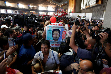 Relative holds a poster of one of the 43 missing students of Ayotzinapa College Raul Isidro Burgos during a catholic service at the at the Basilica of Guadalupe