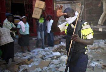 A police officer cleans his face as he take a break while police disperse looters from a commercial area in Port-au-Prince