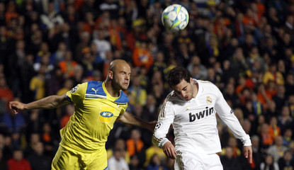 Real Madrid's Higuain and APOEL's Paulo Jorge go for a high ball during their Champions League quarter-final first leg soccer match in Nicosia