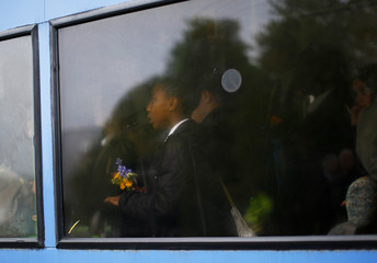 A pupil carries flowers as she arrives by school bus at Corpus Christi Catholic College where teacher Anne Maguire was fatally stabbed in Leeds, northern England