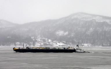 Tugboat pushes a barge south on the Hudson River as snow-covered Hook Mountain and village of Upper Nyack are seen in background during a snowstorm in New York