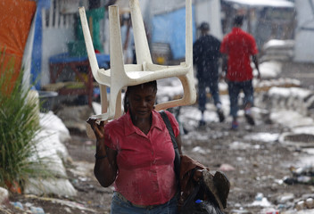 A woman covers herself from the rain with a chair at Petion Ville Club golf course IDP camp in Port-au-Prince
