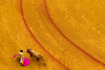 Spanish matador Lopez Simon performs a pass to a bull during a bullfight in the Maestranza bullring in Seville